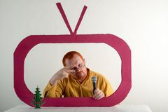 Een mens met rood haar, een baard en een snor in een geel overhemd, glazen parodieert de voorzitters` s toespraak op televisie Ni Stock Foto