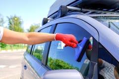 Een mens met een rubberschraper verwijdert de overblijfselen van water uit het glas na het wassen van de auto Schone machine, aut royalty-vrije stock afbeelding