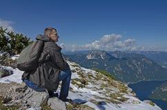 Een mens met een rugzak die een bergmening bewonderen Royalty-vrije Stock Afbeelding