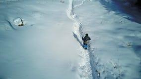 Een mens met een rugzak loopt langs de sneeuwsleep royalty-vrije stock fotografie