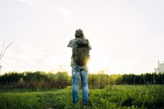 Een mens met een rugzak op zijn rug tegen de achtergrond stock afbeeldingen