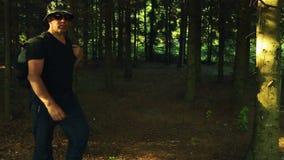 Een mens met een rugzak wandelt door het bos