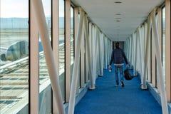 Een mens met een rugzak in zijn handen loopt onderaan de gang om het vliegtuig in te schepen Uit het deel van het venstervoer van stock fotografie