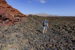 Een mens met een rugzaktrekking in het Nationale Park van Timanfaya Royalty-vrije Stock Foto's