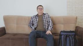 Een mens met scherpe rugpijn gaat naar de bank, zit op het, neemt de telefoon op en telefoneert stock footage