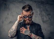 Een mens met tatoos op zijn wapens stock afbeelding