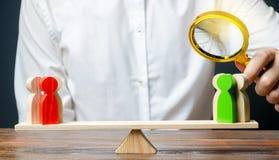Een mens met een vergrootglas bekijkt het afstand houden van groepencijfers aangaande schalen Onderzoekargument van elke kant Con stock afbeelding
