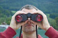 Een mens met verrekijkers Stock Foto