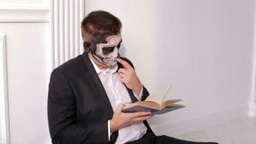 Een mens met een vreselijke samenstelling in de vorm van een schedel houdt een boek Halloween stock video