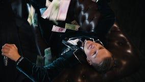 Een mens in modieuze retro kleren die op de laag liggen - geld die neer op hem vallen stock video