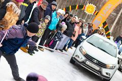 Een mens neemt aan de concurrentie voor de vakantie Maslenitsa deel en sleept een lichtgewichtlada-auto op een kabel Stad van Che stock afbeelding