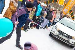 Een mens neemt aan de concurrentie voor de vakantie Maslenitsa deel en sleept een lichtgewichtlada-auto op een kabel Stad van Che royalty-vrije stock afbeelding
