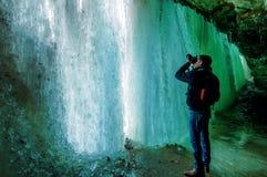 Een mens neemt een beeld van een bevroren waterval stock fotografie