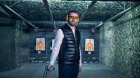 Een mens neemt geladen patroon in een pistool op terwijl status in een het schieten waaier stock footage