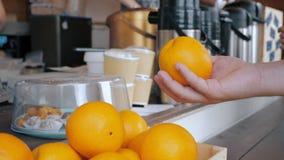 Een mens neemt een sinaasappel van de koffieteller en werpt het in de lucht stock videobeelden