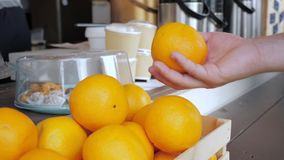 Een mens neemt een sinaasappel van de koffieteller en werpt het in de lucht stock video