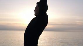 Een mens in ochtendschemer warmt tijdens een vroege ochtendtraining belast op met sport Kaukasische mens die, rek van hem uitoefe stock video