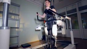 Een mens ondergaat een rehabilitatiezitting in een exoskeleton kostuum stock videobeelden