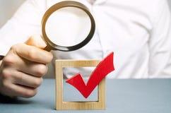 Een mens onderzoekt een rood vinkje door een vergrootglas De beoordeling van van de transparantie van de legitimiteit van een ver royalty-vrije stock foto