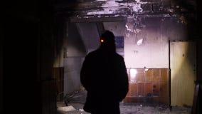 Een mens onderzoekt een verlaten donker huis stock footage