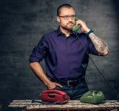 Een mens in oogglazen die de analoge telefoon van de traditiecel met behulp van royalty-vrije stock fotografie