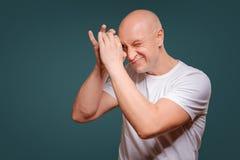 Een mens op een blauwe achtergrond in holding overhandigt dichtbij zijn ogen zoals een telescoop piept stock afbeeldingen