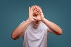 Een mens op een blauwe achtergrond in holding overhandigt dichtbij zijn ogen zoals een telescoop piept stock afbeelding