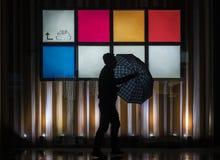 Een mens op de straat in de regenachtige nacht stock fotografie