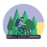 Een mens op een fiets De ritten van een fietsertoerist langs de weg, met een grote toeristenrugzak Royalty-vrije Stock Afbeelding