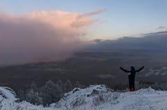Een mens op een heuvel tegengesteld aan wolk royalty-vrije stock afbeelding