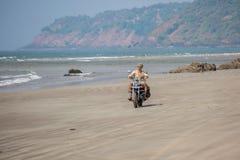 Een mens op een motorfiets berijdt op een verlaten wild strand Royalty-vrije Stock Foto's