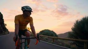 Een mens op een fiets berijdt het bekijken de camera bij zonsondergang op een bergweg Langzame motie Steadicam stock videobeelden