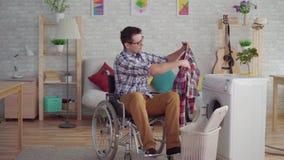 Een mens op middelbare leeftijd met een rolstoel nam in het gebruik van huishoudenkarweien een wasmachine in dienst stock footage