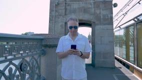 Een mens op middelbare leeftijd in een wit overhemd en zonnebril bevindt zich op de brug stock footage