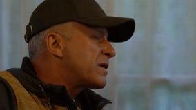 Een mens op middelbare leeftijd zingt een lied met een gitaar De close-up van het gezicht stock video