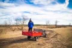 Een mens op een motoblock berijdt een gebiedsweg in de lente in Maart royalty-vrije stock foto
