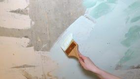Een mens op een sjofele grijs-witte muur veroorzaakt een borstel blauwe verf met lichte slagen stock video