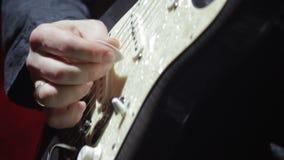 Een mens op stadiumspelen op een witte elektrische gitaar, close-up stock videobeelden