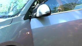 Een mens opent de autodeur stock video