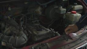 Een mens opent de kap van een auto bij een benzinestation en een technisch onderzoek voor diagnostiek stock videobeelden