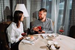 Een mens opent een giftdoos op een datum Zijaanzichtportret van lachend paar die van datum in koffie genieten royalty-vrije stock afbeeldingen