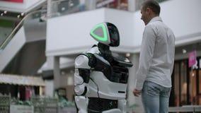 Een mens in een overhemd communiceert met een witte robot die vragen stellen en het scherm met zijn vingers drukken stock videobeelden