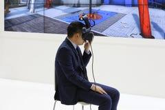 Een mens in een pak zit op een stoel De man draagt virtuele werkelijkheidsglazen royalty-vrije stock foto