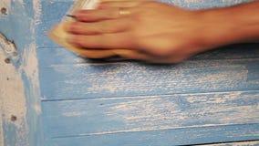 Een mens poetst houten raad met een stuk van schuurpapier op stock footage