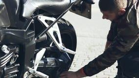 Een mens poetst een motorfiets met een doek op een wasmachine op stock footage