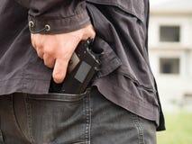Een mens, een politieagent of een rover, gangster die zijn kanon achter zijn rug verbergen stock foto