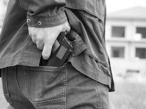 Een mens, een politieagent of een rover, gangster die zijn kanon achter zijn rug verbergen stock afbeelding