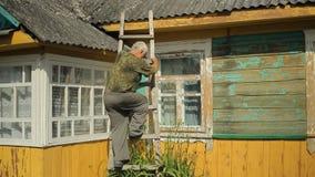 Een mens probeert om het dak te bevestigen Hij bevindt zich op de treden dichtbij het huis stock footage