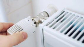 Een mens regelt de temperatuur in het huis met een thermostaat op de radiator stock videobeelden