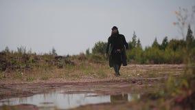 Een mens in een regenjas en een hoed met een baard en ontzetting ontspant zijn rug die van de grond opstaat stock footage